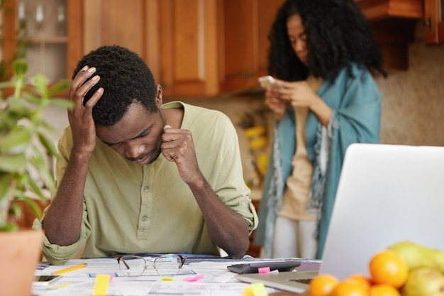 Arbeitsloser junger afroamerikanischer mann, der unter finanziellem stress steht, sich depressiv und frustriert fühlt