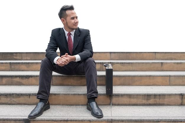 Arbeitsloser junger geschäftsmann, der auf treppe in der stadt sitzt