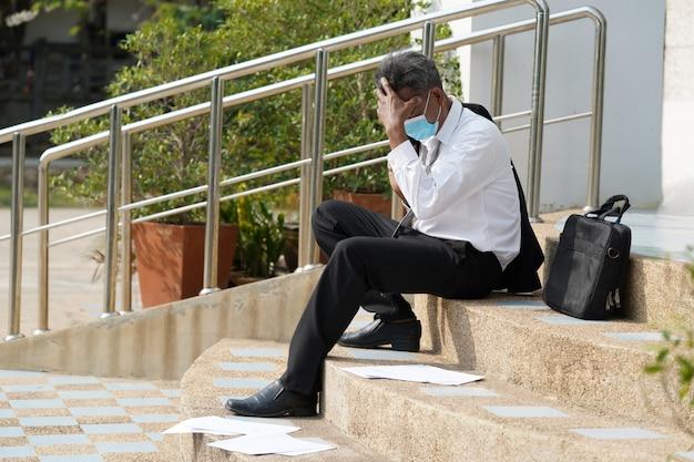 Arbeitsloser mann, verzweifelter geschäftsmann, der wegen arbeitslosigkeit hoffnungslos auf der treppe im zentralen geschäftsviertel sitzt