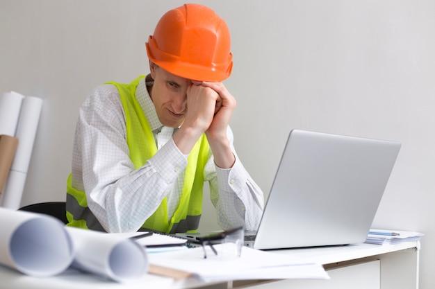 Arbeitslosigkeit. mann baumeister ingenieur in einem helm, ohne arbeit, depression und verzweiflung