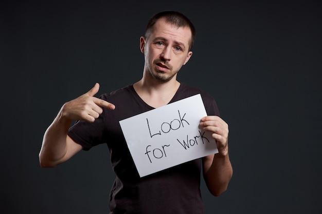 Arbeitslosigkeit und krise mit mann, der ein zeichen mit den wörtern hält, die arbeit suchen