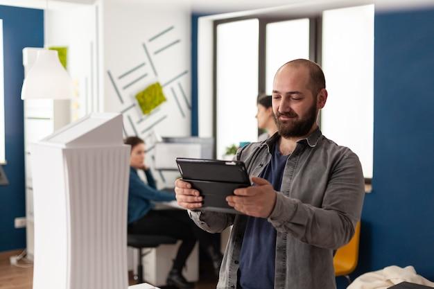 Arbeitsmanagermann, der auf tablet im architekturbüro schaut
