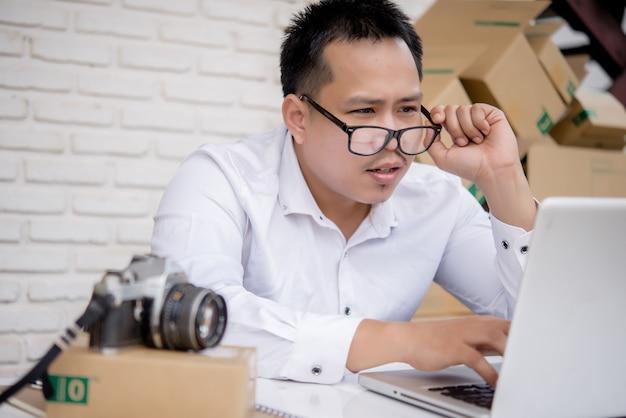 Arbeitsmarketing des jungen mannes online mit laptop- und kastenbeitrag