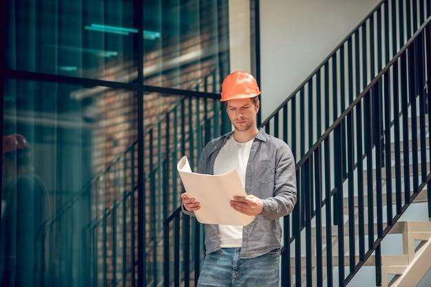 Arbeitsmoment. aufmerksamer junger erwachsener mann mit schutzhelm, der sich die skizze auf dem papier in den händen ansieht, die in einem neuen modernen gebäude stehen