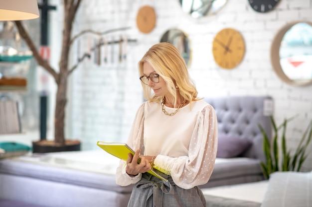 Arbeitsmoment. blonde frau mit brille, die im ausstellungsraum mit einem großen gelben notizbuch in ihren händen steht und sie mit interesse ansieht.