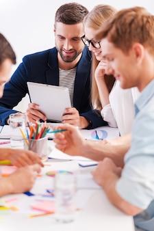 Arbeitsmomente. gruppe fröhlicher geschäftsleute in eleganter freizeitkleidung, die zusammenarbeiten, während sie am tisch sitzen