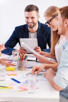 Arbeitsmomente. gruppe von geschäftsleuten in eleganter freizeitkleidung, die zusammen am tisch sitzen und lächeln