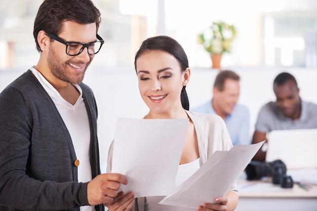 Arbeitsmomente. zwei fröhliche geschäftsleute, die dokumente halten und lächeln, während zwei leute am hintergrund arbeiten