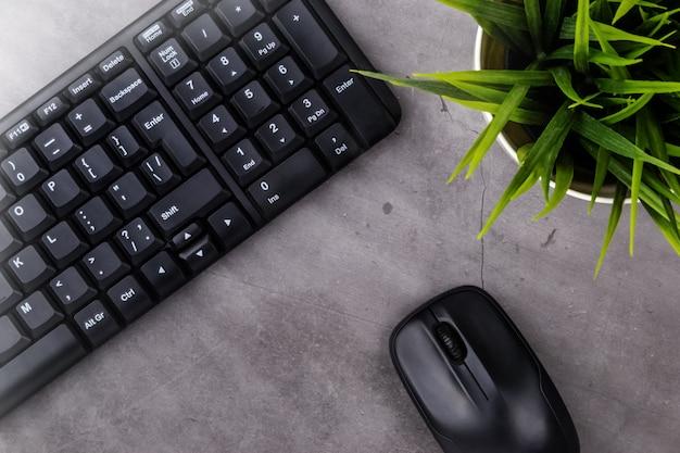 Arbeitsplatz auf dunklem tisch. tabelle mit tastatur, computermaus, blume im topf. flach liegen. draufsicht, die sonnenstrahlen von der seite.