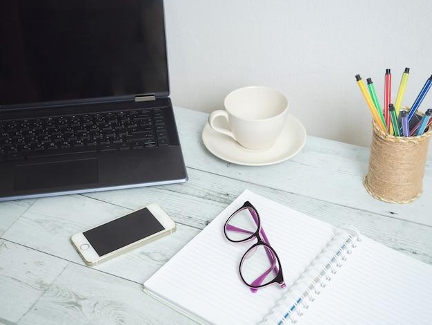 Arbeitsplatz auf holztisch, laptop-notebook-brille, kaffeetasse und handy auf dem tisch