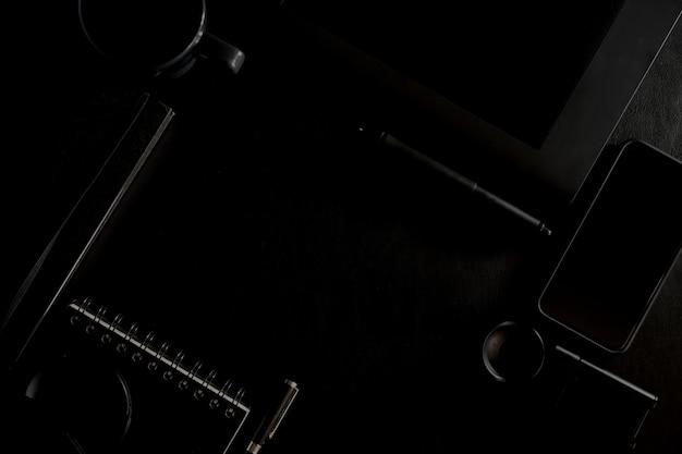 Arbeitsplatz auf schwarzer lederner spitzentabelle eines kreativen designers oder eines fotografen und kopienraum