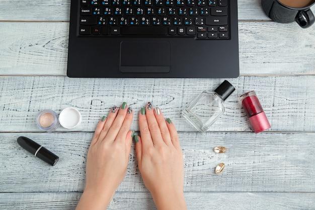 Arbeitsplatz der frau mit laptop, kaffeetasse und kosmetik