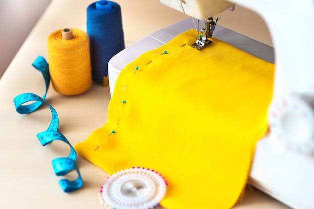 Arbeitsplatz der näherin. professionelle nähmaschine bei der arbeit. nähmaschine näht bunte textilien, meter- und farbige fäden zum nähen