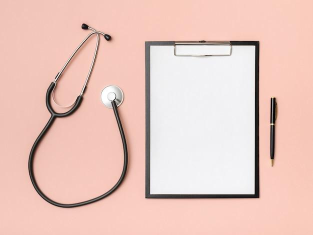 Arbeitsplatz des arztes mit notizbuch und stethoskop