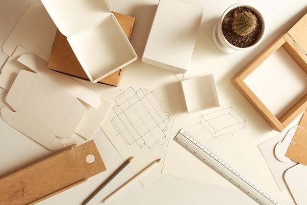 Arbeitsplatz des designers der pappverpackung. papierkästen skizzieren.