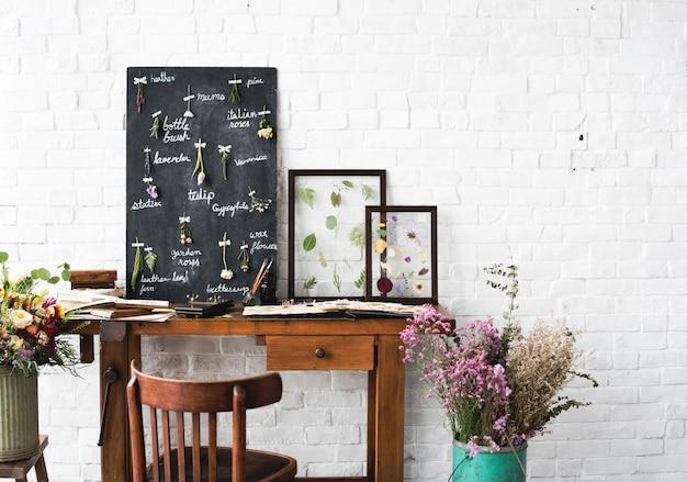Arbeitsplatz des floristen mit trockenen blumen-namensliste auf schwarzem brett