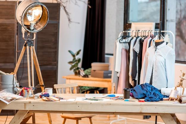 Arbeitsplatz des modedesigners mit schneiderwerkzeugen und zeichnungen auf dem tisch mit kleidung im hintergrund