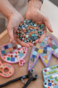 Arbeitsplatz des mosaikmeisters: frauenhände, die mosaikdetails bei der herstellung eines mosaiks halten