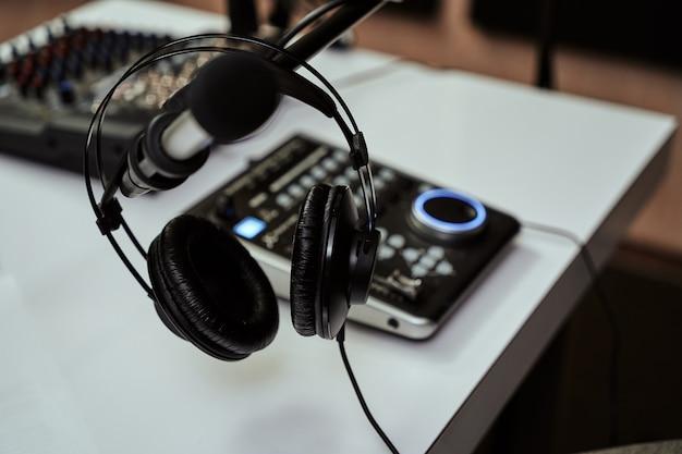 Arbeitsplatz des radiomoderators nahaufnahme von kopfhörermikrofon und tonmischpult auf dem tisch in