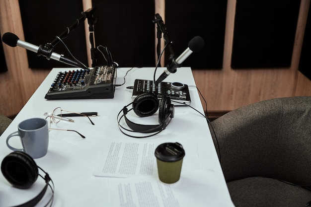 Arbeitsplatz des radiomoderators, nahaufnahme von mikrofonen, kopfhörern, tonmischpult-skript auf dem