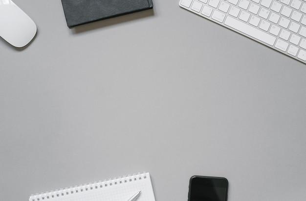 Arbeitsplatz eines büroangestellten oder freiberuflers tastatur, maus, segelflugzeuge und tagebücher, kugelschreiber, telefon auf einem grauen hintergrund mit kopierraum.