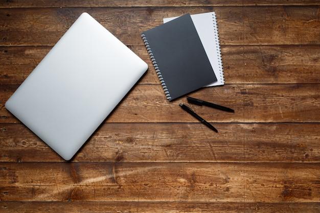 Arbeitsplatz eines kaufmanns. sicht von oben . kaffee notebook und laptop auf dem desktop mit schwarzer note.