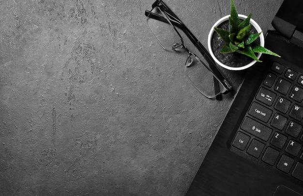 Arbeitsplatz für freiberufler. laptop, blume und gläser auf einem dunklen betonhintergrund. speicherplatz kopieren