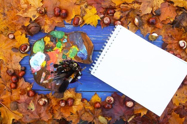 Arbeitsplatz für maler im herbstpark mit palette, papierblock und pinseln. herbstblätter und kastanien auf blauem hintergrund aus holz.