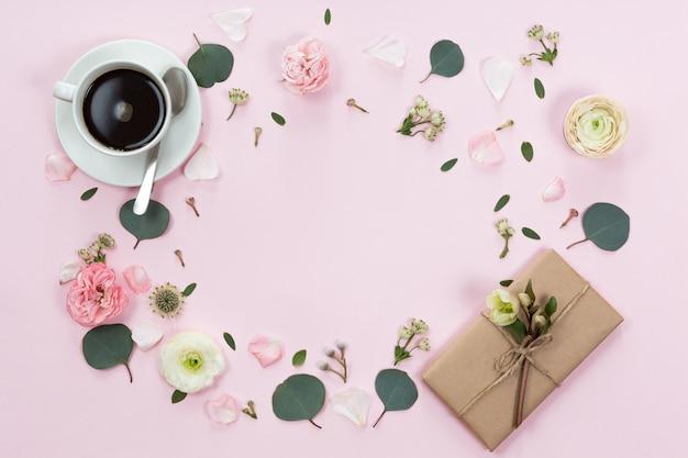 Arbeitsplatz. geschenk, tasse kaffee und rosenblüten. flache lage, draufsicht, kopienraum