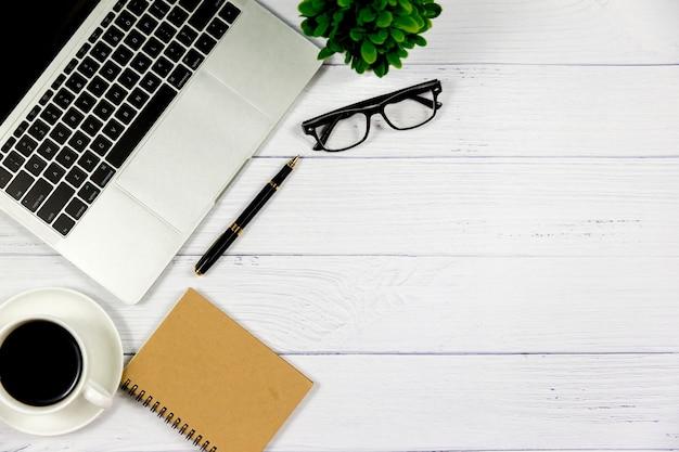 Arbeitsplatz im büro, im hölzernen weißen schreibtisch mit leerem notizbuch und in anderem büroartikel