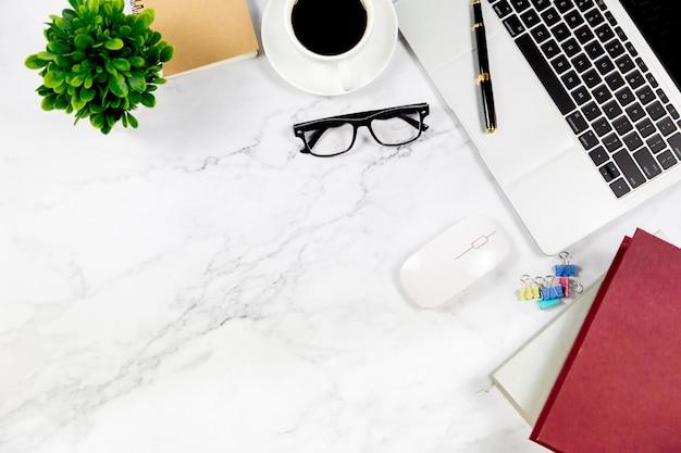 Arbeitsplatz im büro, im weißen marmorschreibtisch mit leerem notizbuch und in anderem büroartikel