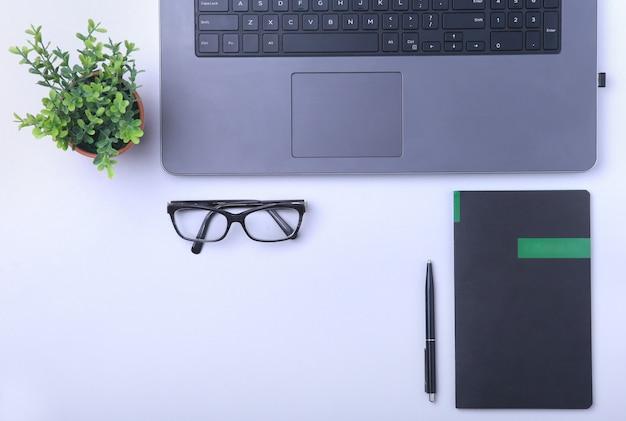 Arbeitsplatz im büro mit laptop, notebook, brille und anderen geräten.