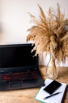 Arbeitsplatz im homeoffice mit einem holzschreibtisch. blick von oben auf die tastatur mit notebook, stift, smartphone, pampa. raum für moderne kreative arbeit des designers. geschäfts- und finanzkonzept.