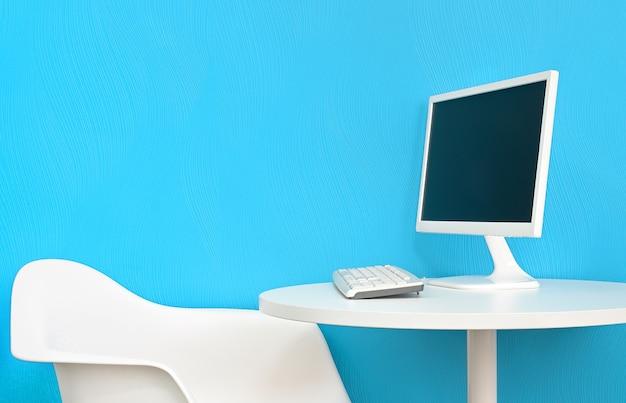 Arbeitsplatz im kleinen büro. computermonitor auf dem weißen tisch und stuhl auf blauem wandhintergrund