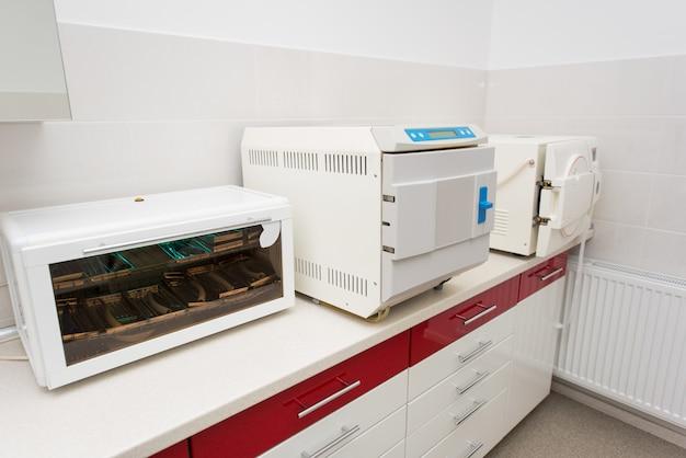 Arbeitsplatz in der zahnheilkunde. tisch mit uv-regal, sterilisator, autoklavieren