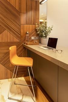 Arbeitsplatz in wohnung oder café mit modernem interieur. öffnen sie den laptop und die brille auf der tischplatte.