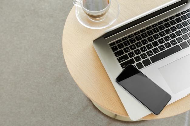 Arbeitsplatz: laptop, telefon und ein getränk