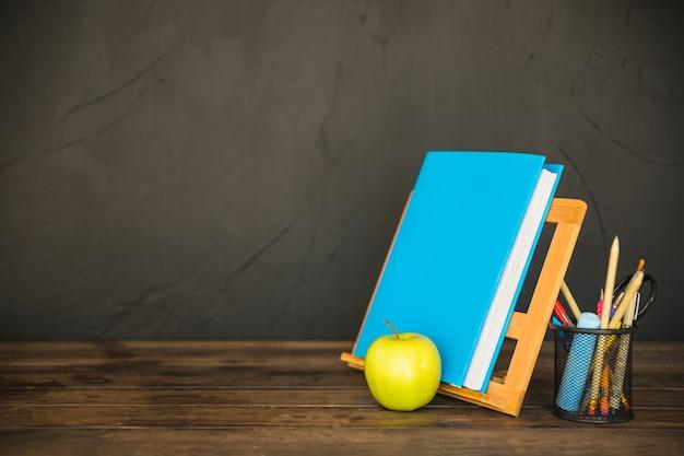 Arbeitsplatz mit buchstand mit buch auf tabelle mit briefpapier