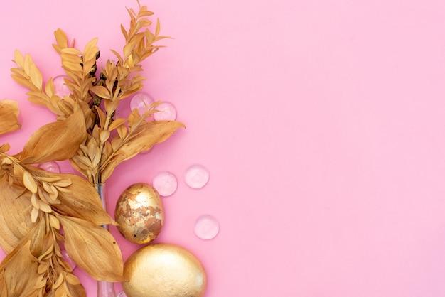Arbeitsplatz mit computer, blumenstrauß ranunculus und rosen, klemmbrett, weibliches goldenes mode-accessoire lokalisiert auf rosa hintergrund.