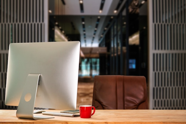 Arbeitsplatz mit computer, laptop, bürobedarf und kaffeetasse, smartphone und tablet im büro. schreibtischarbeitskonzept. im morgenlicht