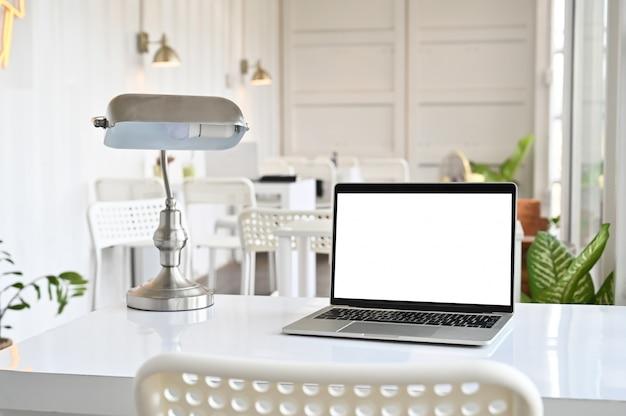Arbeitsplatz mit computerlaptop und -lampe auf bürotisch mit montageschirm.