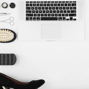 Arbeitsplatz mit dem laptop- und modezubehör der frauen lokalisiert auf weißem hintergrund