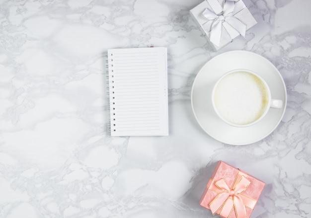 Arbeitsplatz mit einer tasse kaffee, einer schwarzen notiz und geschenkboxen auf einem marmortisch. draufsicht, flache lage, kopierraum