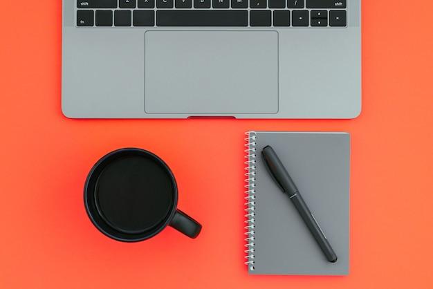 Arbeitsplatz mit farbiger oberfläche. laptop, eine tasse kaffee, ein notizblock mit einem stift lokalisiert auf einem roten hintergrund