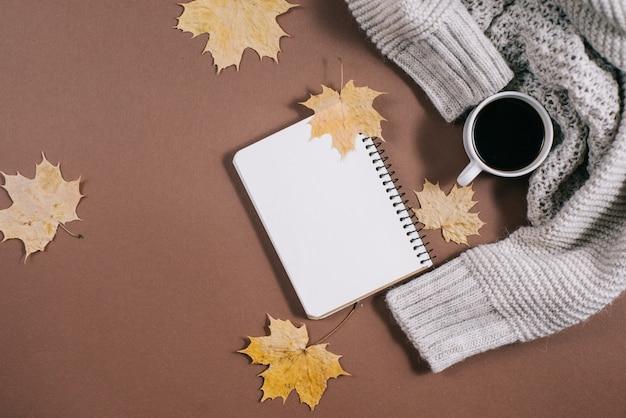 Arbeitsplatz mit goldenen ahornblättern, notizbuch, kaffeetasse, strickjacke auf braunem hintergrund.