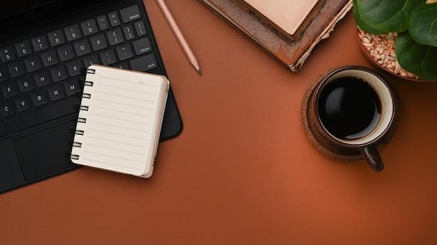 Arbeitsplatz mit kaffeetasse, notebook, tastatur und kopierraum braunes leder.