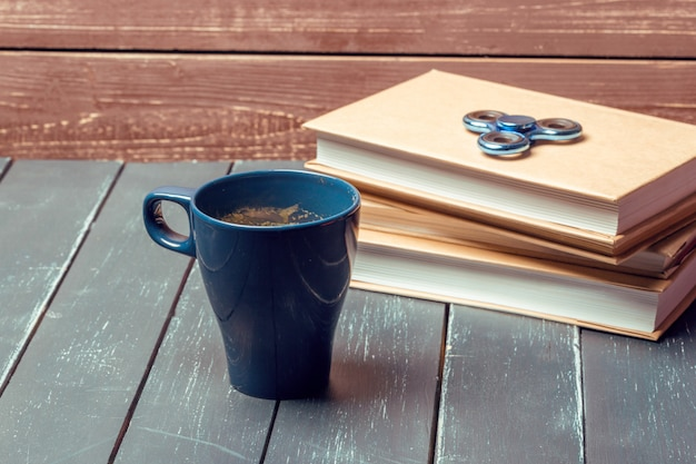 Arbeitsplatz mit kaffeetasse, spinner und buch
