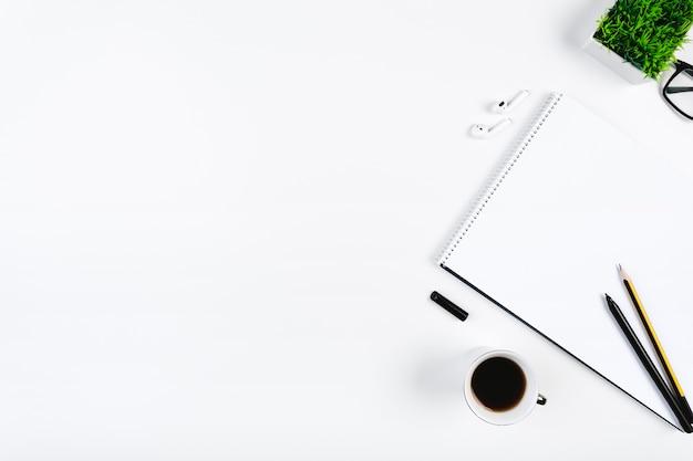Arbeitsplatz mit kaffeetasse und notizbuch