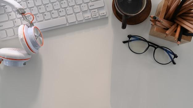 Arbeitsplatz mit kopfhörer, kaffeetasse, tastatur, brille und kopierraum auf weißem tisch.