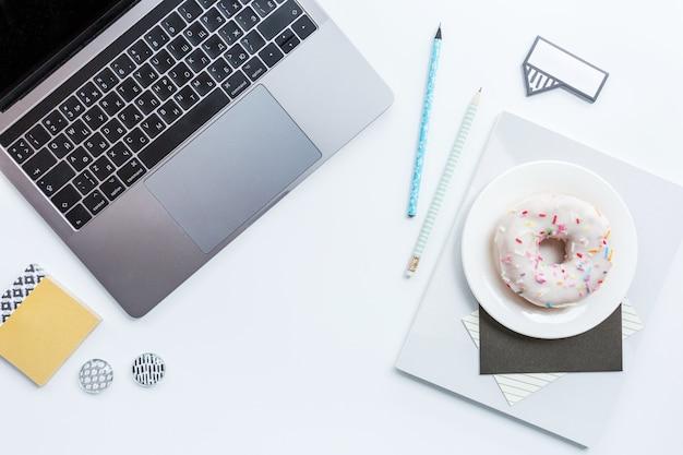 Arbeitsplatz mit laptop, bleistift, notizbuch und donut auf weißem hintergrund